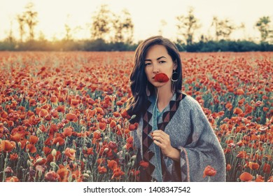 Fashionable beautiful brunette young woman holding red poppy near her face in flower field, looking at camera.