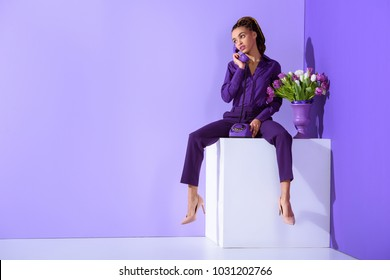 fashionable beautiful  girl talking on rotary phone and sitting on cube with tulips
