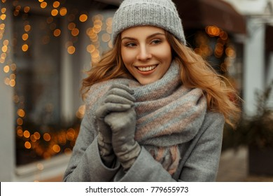 Fashionable beautiful happy woman with a smile in knitwear clothes with a knitted hat in a gray coat on a winter holidays on the street. Festive lights background