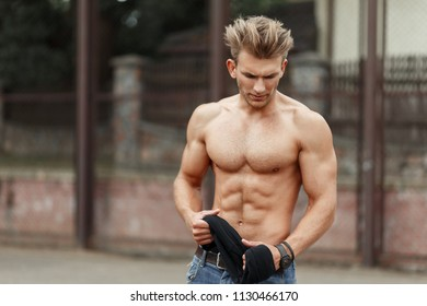 Fashionable beautiful sports model man with a hairdo with a healthy body with muscles on the street
