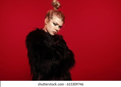 Fashionable beautiful woman in a black fur coat of artificial fur on a red background stands frowning