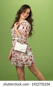 Fashionable beautiful woman in nice dress. Fashion spring summer photo. Green background