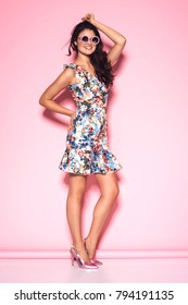 Fashionable beautiful woman in sunglasss and nice dress. Fashion spring summer photo. Pink background