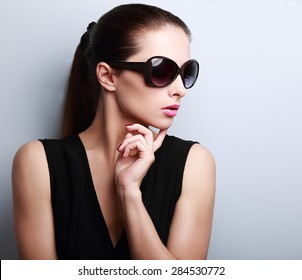 Fashionable beautiful young female model profile in sun glasses posing on blue background