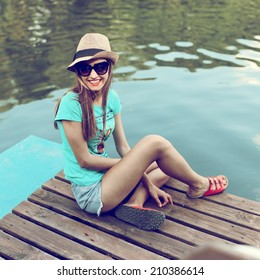Fashionable beautiful young girl in hat and sunglasses sitting on the boat and laughing