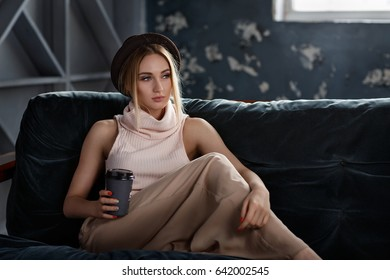 Fashionable beautiful young girl sits on the couch with a glass of fresh coffee in a cozy atmosphere