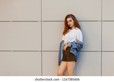 Fashionable beautiful young stylish woman model in vintage jeans clothes in a gray T-shirt with shorts near a modern wall
