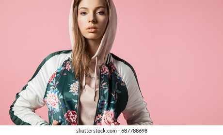 Fashionable beautiful young woman in a bomb jacket with floral print stands on a pink background