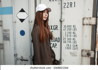 Fashionable beautiful young woman with a clean white cap for moke up posing near a meta container