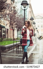 Fashionable beautiful young woman with coffee walking on street and texting on cell phone