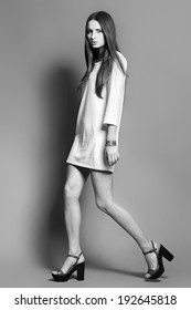Fashionable beautiful young woman posing in studio, black and white shot