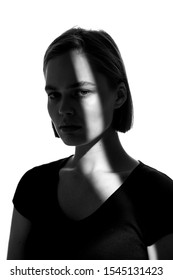Fashionable beauty portrait. Black silhouette on white background. Girl with a spot of light on her face.