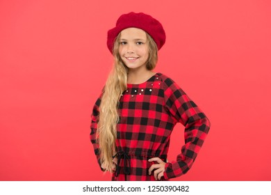 Fashionable beret accessory for female. Beret style inspiration. Wear beret like fashion girl. Kid little cute girl with long blonde hair posing in beret hat and checkered dress red background.