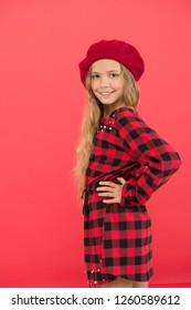 Fashionable beret accessory for female. Wear beret like fashion girl. Kid little cute girl with long blonde hair posing in beret hat and checkered dress red background. Beret style inspiration.
