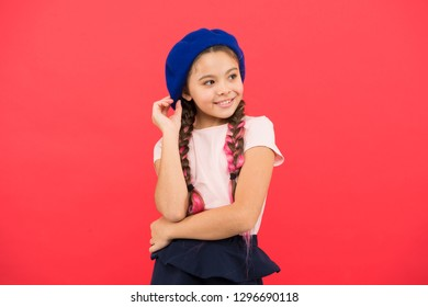 Fashionable beret accessory. Teenage fashion. French fashion attribute. Child small girl happy smiling baby. Kid little cute fashion girl posing with long braids and hat red background. Fashion girl.