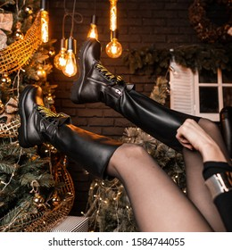 Fashionable black leather shoes with yellow shoelaces on female legs in the air on the background of the Christmas tree and vintage lamps. Trendy collection of seasonal women's shoes. Close-up.