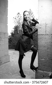 Fashionable black and white photo from a magazine. beautiful young rocker in a heavy leather jacket, with long beautiful black hair posing on the background grid and arch