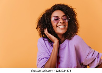 Fashionable black woman posing on colorful background with cheerful smile. Optimistic african girl in purple sweater looking to camera.