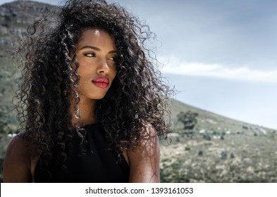 Fashionable black woman with red lips posing looking away with mountains in the background