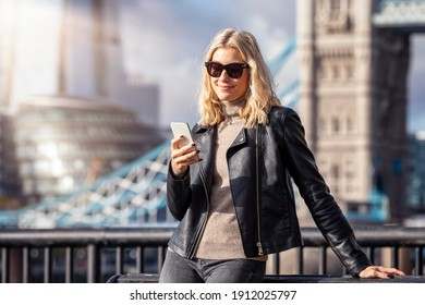 A fashionable, blonde city woman with a black leather jacket checks her mobile phone in front of the city skyline of London
