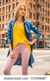 Fashionable blonde woman in jeans coat and nice clothes, yellow purse walking in the street. Fashion spring autumn photo