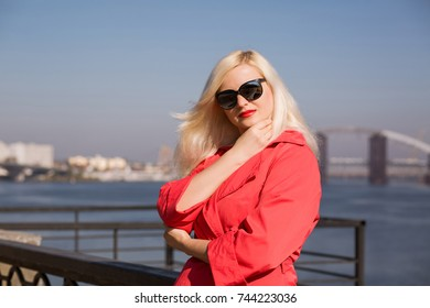 Fashionable  blonde woman posing in red cloak, wears sunglasses on a blurred bridge background