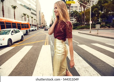 Fashionable blonde woman in red top and nice gold skirt, sunglasses walking in the street. Fashion spring summer photo