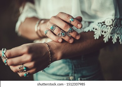 Fashionable boho chic woman in a white short blouse with silver turquoise jewelry. Boho fashion. Stylish girl wearing silver rings with turquoise stone in hippie style.