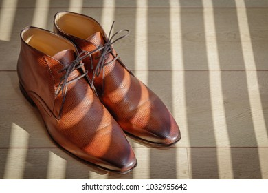 fashionable brown leather men's shoes on a light wooden floor