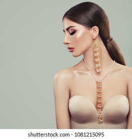 Fashionable Brunette Model with Gold Jewelry. Young Woman with Ponytail Hairstyle, Necklace and Earrings