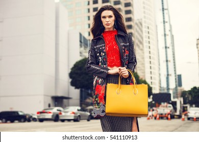 Fashionable brunette woman in a coat and nice dress, yellow handbag walking in the street. Fashion autumn photo