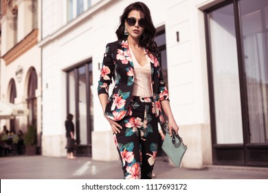 Fashionable brunette woman dressed in nice clothes, sunglasses walking in the street. Fashion spring summer photo