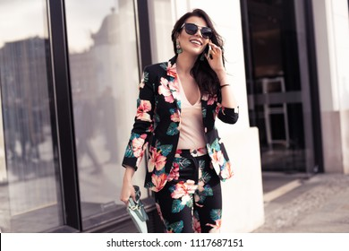 Fashionable brunette woman holding a smartphone, talking on the phone.  Dressed in nice clothes, sunglasses walking in the street. Fashion spring summer photo