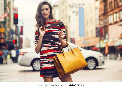 Fashionable brunette woman in a nice dress, over knee boots, yellow handbag walking in the street. Fashion spring summer autumn photo