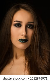 Fashionable brunette woman with perfect skin and creative metallic green makeup. Closeup portrait at studio on a dark background