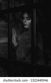 Fashionable brunette woman wearing blouse posing behind the glass door. Black and white toning