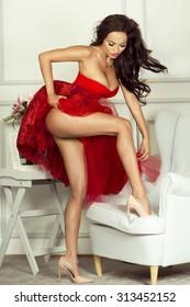 Fashionable brunette woman wearing red elegant dress, showing slim legs.
