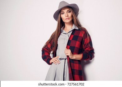 Fashionable brunette young woman in nice clothes posing in the studio. Wearing red sweater, handbag, hat, dress and high heel boots. Autumn photo