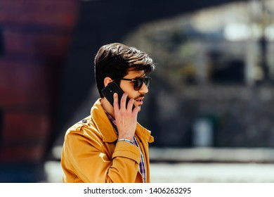 Fashionable businessman walking on city square while talking on mobile, calling for a ride, e-hailing