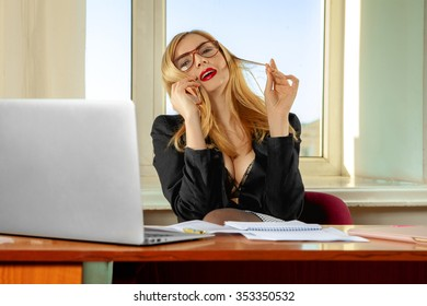 Fashionable busty secretary talking phone in office. Business concept