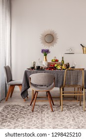 Fashionable chairs at dining room fable full of food and fruits