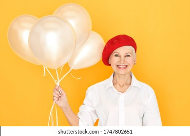 Fashionable cheerful European female pensioner in white shirt and red bonnet holding helium balloons and smiling, celebrating anniversary or birthday, having happy overjoyed facial expression