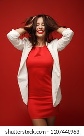 Fashionable, cheerful girl in a red dress and a white jacket shatters her hair isolated on a red background.