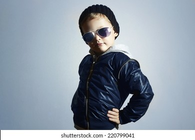Fashionable child in sunglasses. Kid in Black cap.winter style.Posing Little boy.Children fashion.Blue background