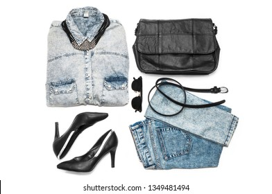 Fashionable clothes and accessories. Denim shirt, necklace, black heeled shoes, jeans, bag, belt and sunglasses, isolated on a white background. Flat lay. Top view. Trends. Stylish lady