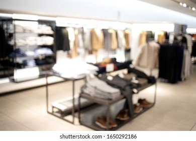Fashionable clothing store in shopping center. Sale and seasonal change of collection. Led lighting on the ceiling. Fire system and air conditioning system in retail shop. Blurred.