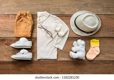 Fashionable concept, clothing set children's clothes with boy shoe, shirt, pants, socks, eyeglasses, hat and teddy bear on wooden background. pack shots, top view