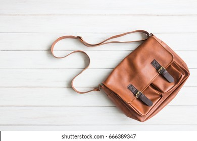 Fashionable concept, men's casual outfits with leather accessories, brown bag on white wooden board background