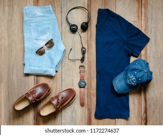 Fashionable concept, men's clothes with loafer shoe, blue shirt, denim shorts, watch, earphone, sunglasses and denim cap on wooden background. pack shots, top view