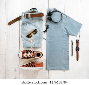 Fashionable concept, men's clothes set with sneakers, shirt, denim shorts, watch, sunglasses, belt, earphone and bracelet on white wooden background. pack shots, top view
